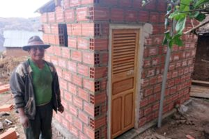 A Bolivian man wearing a hat and a green shirt standing beside a small red-brick building