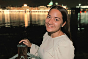Adrienne Sauer at night wearing a white blouse and standing by water