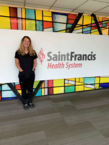 woman in black top and pants standing in front of a sign that reads Saint Francis Health System