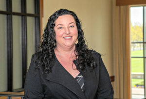 Woman with long dark hair wearing a black blazer and smiling