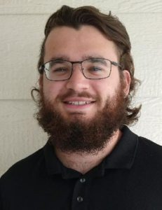 Young man smiling with beard and glasses