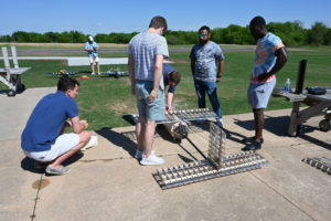 group of five young men outdoors assembling a glider
