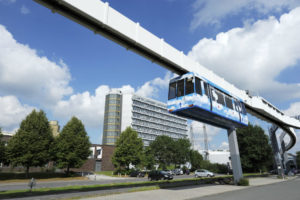 suspended monorail transportation system in front of a large building