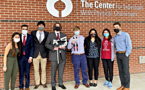 eight people wearing face masks standing in front of a brick wall with the words The Center for Individuals with Physical Challenges
