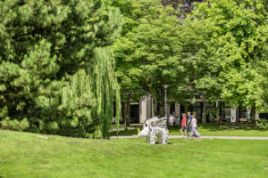 Students walking among trees and across green grass near a statue of white flying rhinoceros