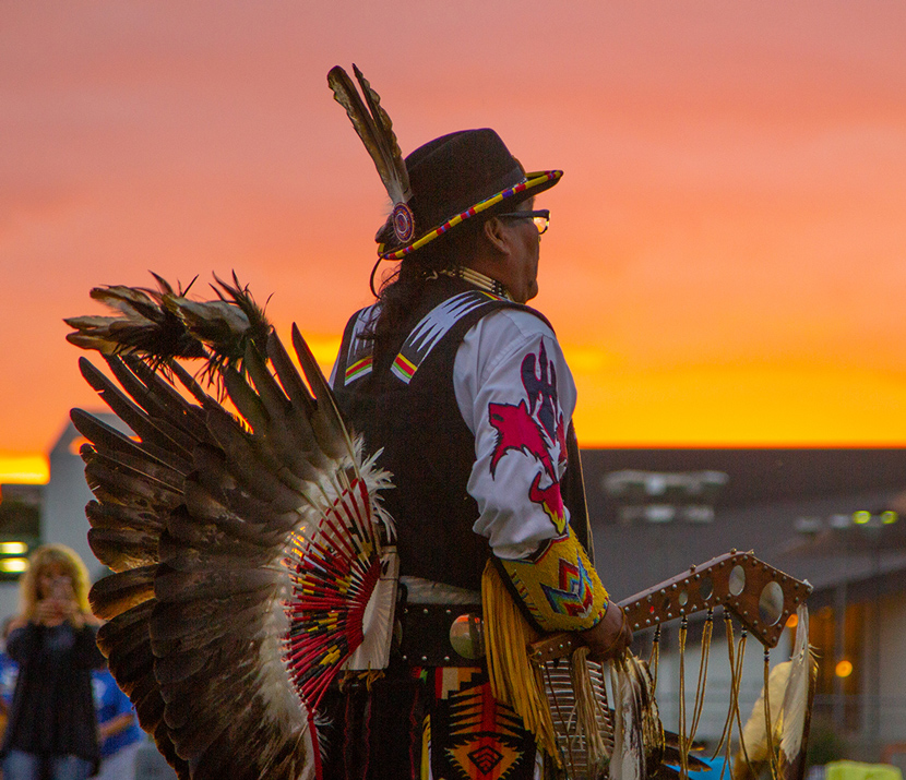 Native American man with features powwow at sunset