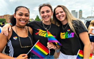 three young women smiling outdoors and holding small LGBTQ+ rainbow flags