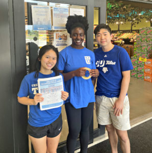 Three people in blue t-shirts standing outside a grocery store