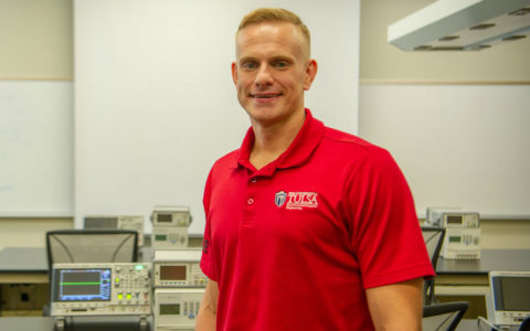 tall man in a red polo shirt standing in an electrical engineering classroom