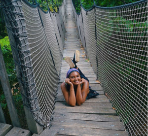 woman smiling while laying down on the floor of a long wooden suspension bridge
