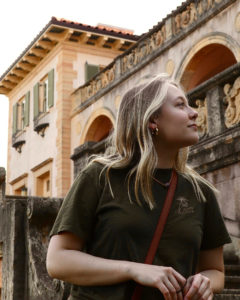 woman with long blonde hair standing outdoors gazing at a building